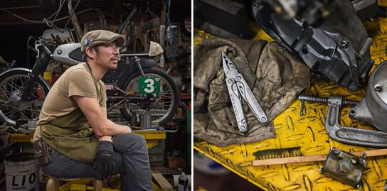 Motorcycle mechanic taking a break, sitting beside the motorcycle he's rebuilding with all his tools including Leatherman Charge TTI multi-tool.