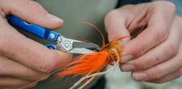 Snipping fishing tackle off a fishing line with Leatherman Micra multi-tool.