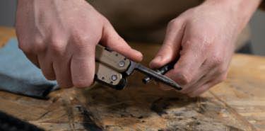 Using carbon scraper on Leatherman Super Tool® 300M for firearm maintenance.
