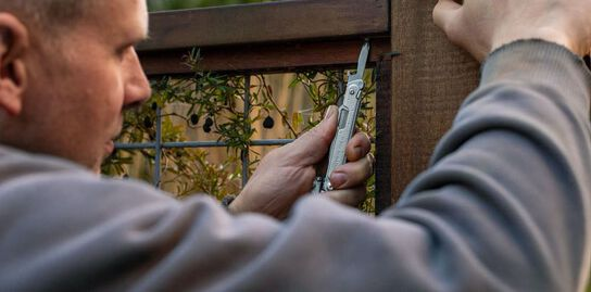Man using Leatherman FREE P4 to screw in a fence grating.