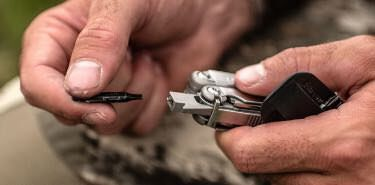 Outdoorsmen switching the bit in Leatherman Wave multi-tool.
