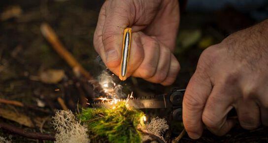 Encendiendo una fogata con la varilla de ferrocerio de la herramienta multiusos de supervivencia en la naturaleza Leatherman Signal®.