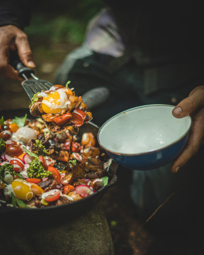 Scooping the cast iron chorizo hash into a bowl.