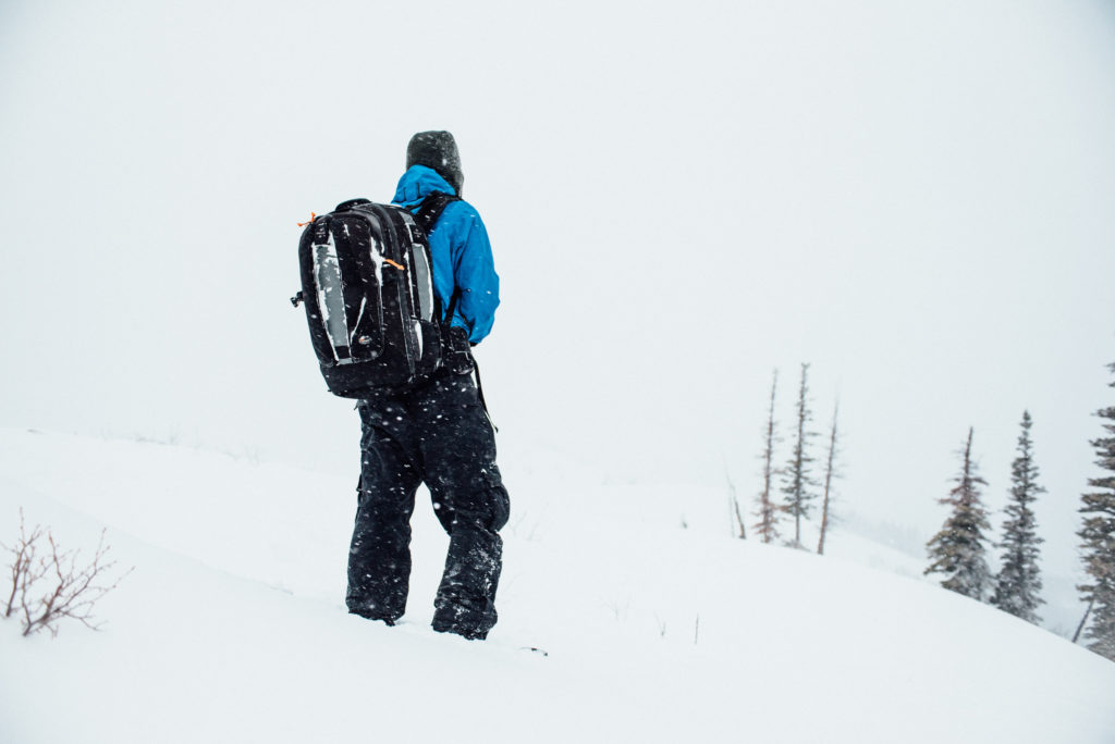 Photographer Isaac Miller out in the snow with his camera equipment. A cold, snowy day capturing scenic images in the Wasatch Mountains of Utah.