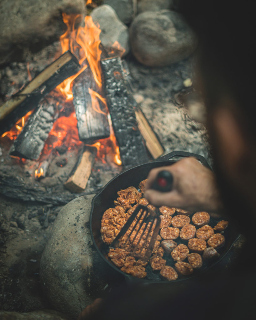 Cooking the chorizo sausage in a cast iron pan over a fire.