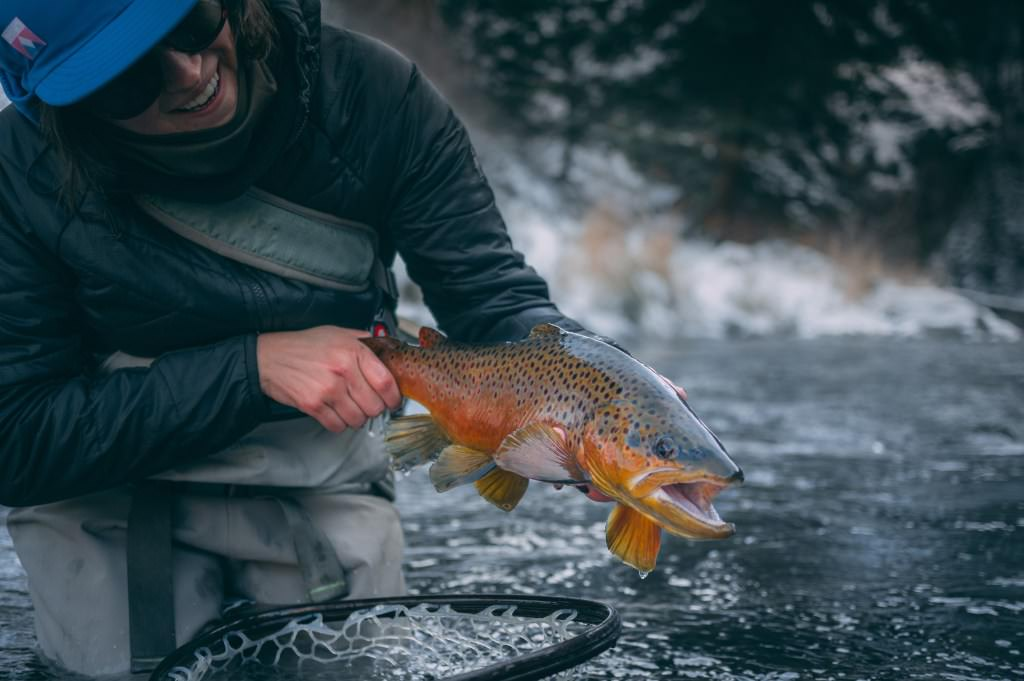 Jean Marie in a winter river setting with a fish in hand.