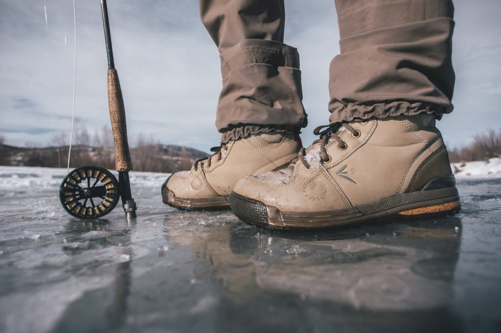 Standing on ice with a fly rod and winter boots.