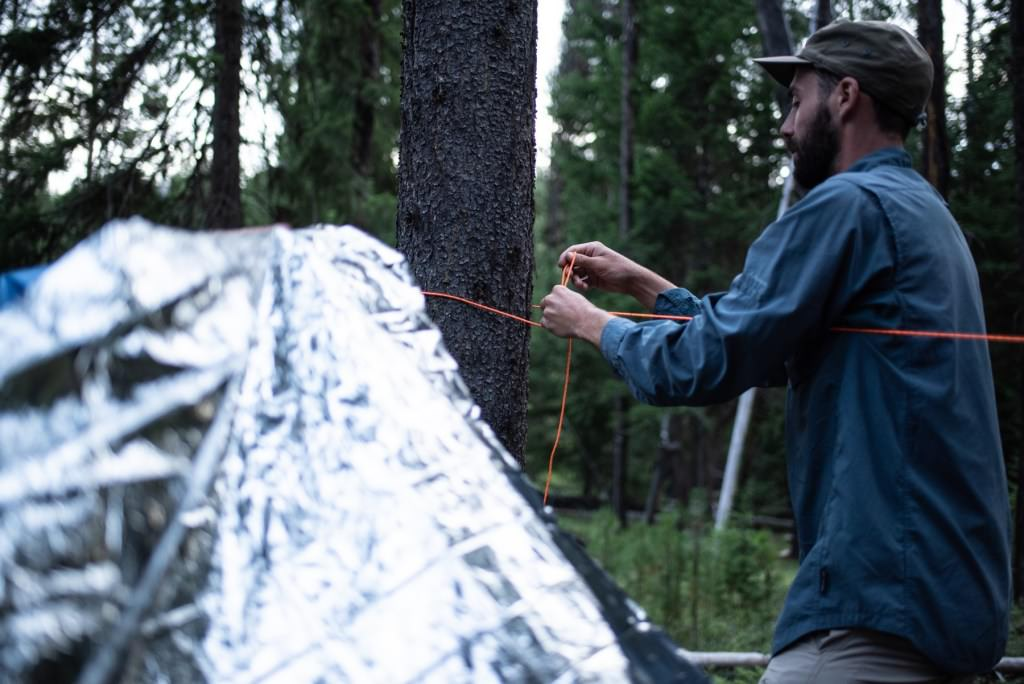 Man setting up emergency blanket in forest.