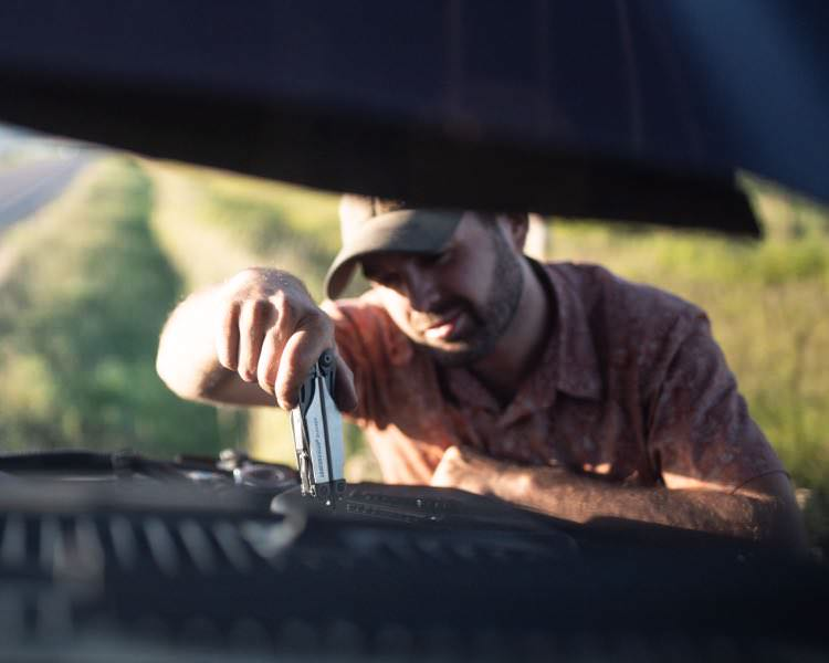 Man using Leatherman Surge multi-tool to work under the hood of his automobile.
