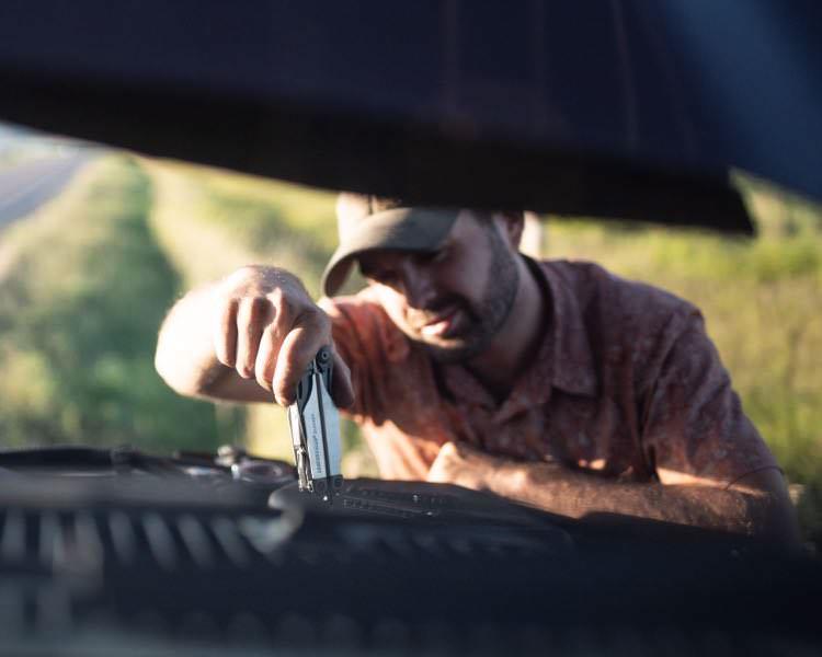 Homme sous le capot d'une voiture utilisant le multi-outils Surge Leatherman pour faire des réparations.