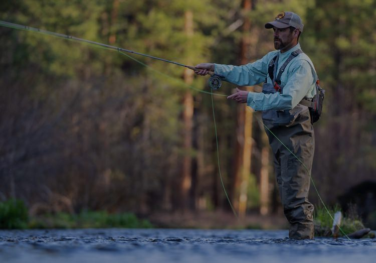 Fly fisherman fishing fresh water forest stream.