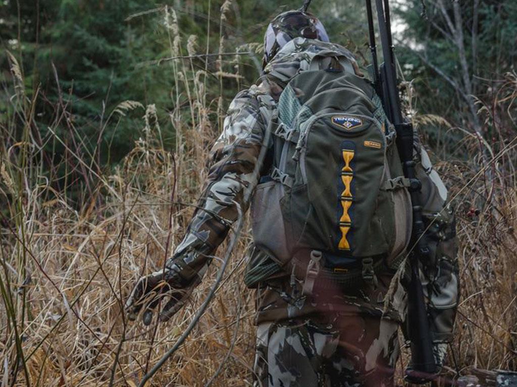 hunter walking through tall grass