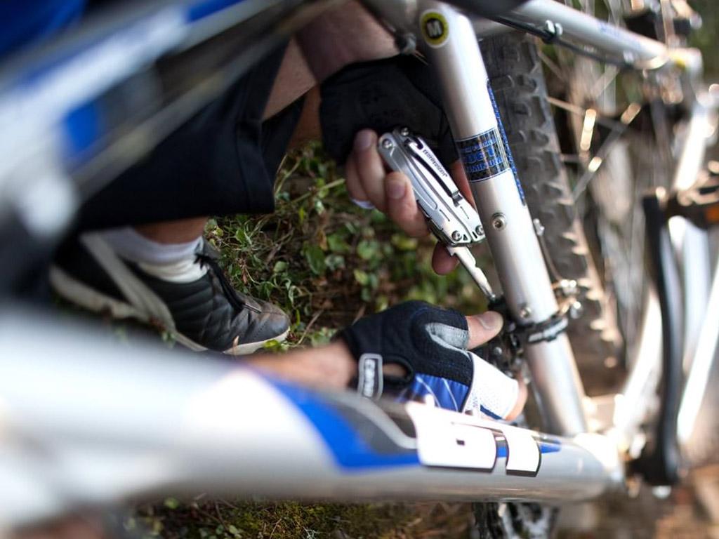 biker fixing bike with leatherman tool