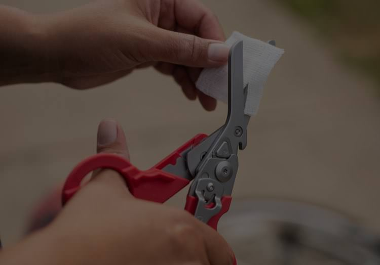 Red Leatherman Raptor being used to cut bandage
