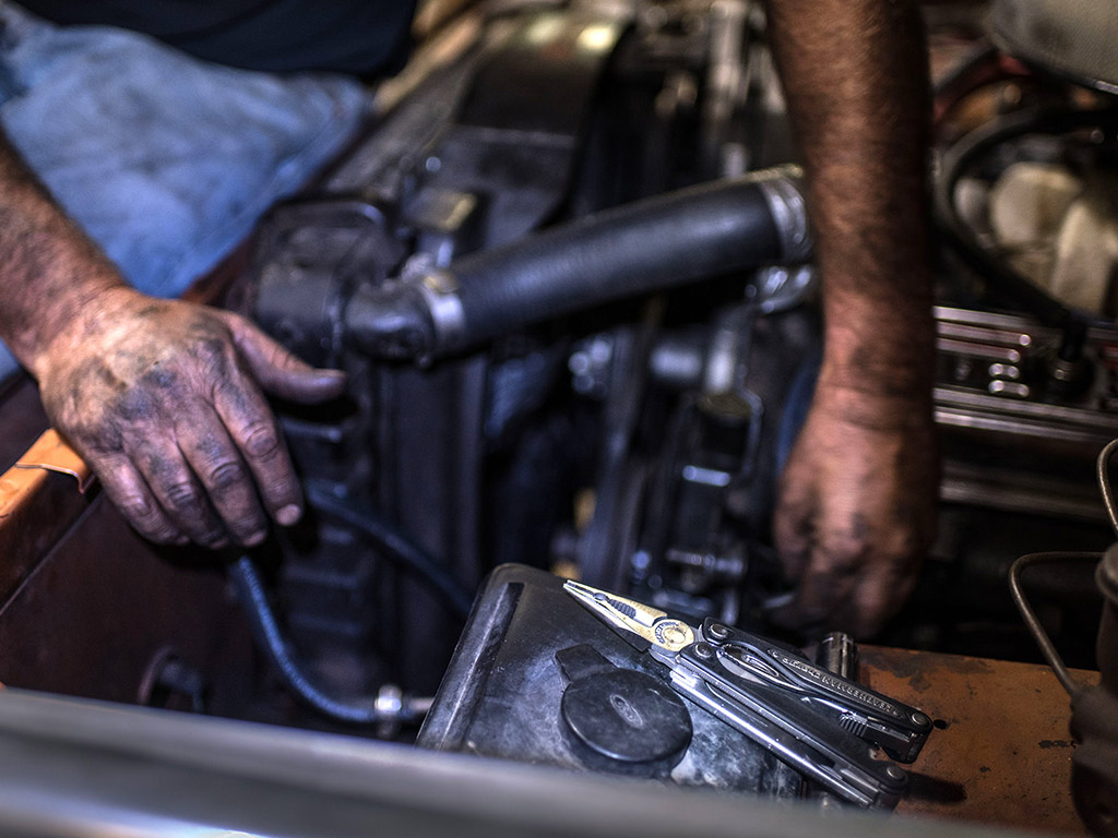 Mechanic fixing car with Leatherman tool
