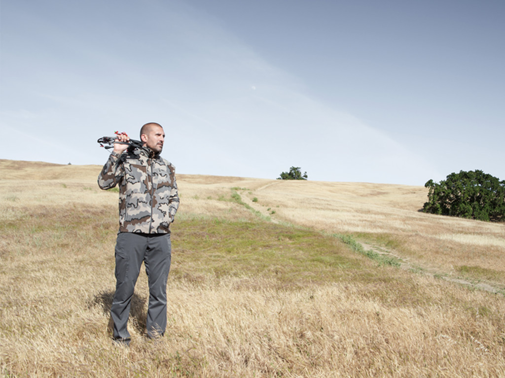 hunter standing in field with bow