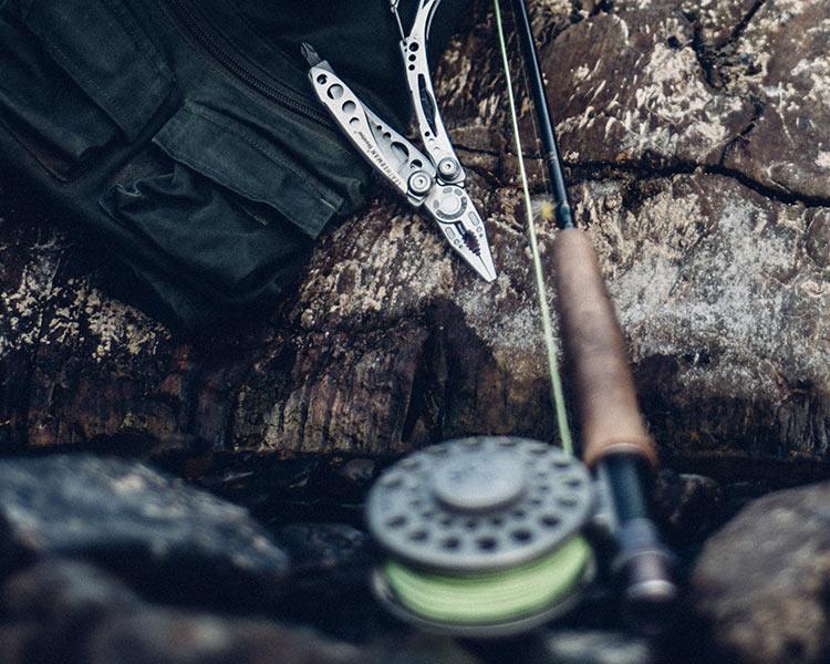 Bag, Leatherman Skeletool, Fishing Rod against rock