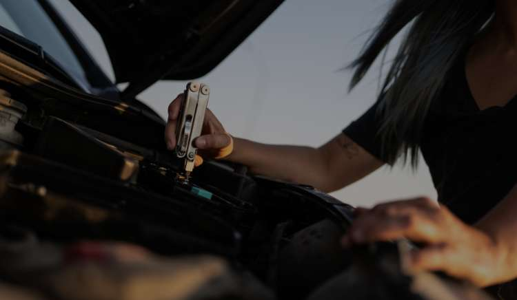 Person working on vehicle with leatherman curl