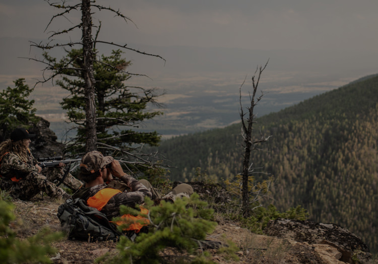 Two rifle hunters atop a mountain using binoculars to scout for deer or elk.