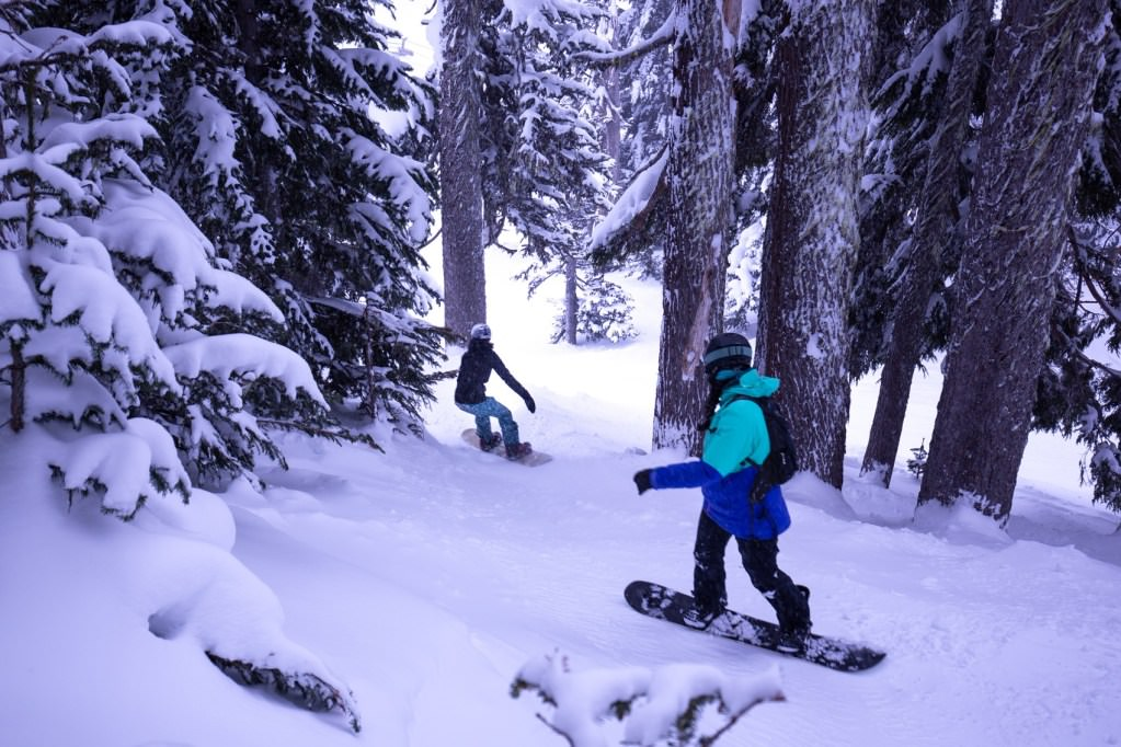 Two snowboarders navigate their way through the trees up at Mt. Hood Meadows.