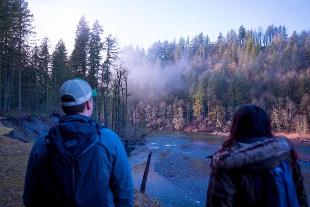 Two hikers taking in the view of a foggy Sandy river in Oregon.