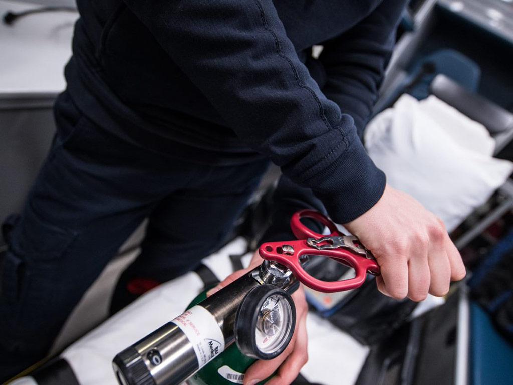 Medic using oxygen tank wrench on oxygen tank