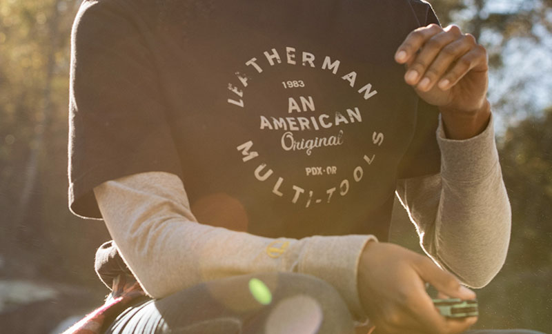 Camper wearing Leatherman Heritage Badge Tee in black holds an Aqua Leatherman Signal multi-tool.