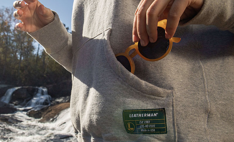 Sashing sunglasses in the front pouch of the Leatherman Basics Pullover Hoodie in gray.