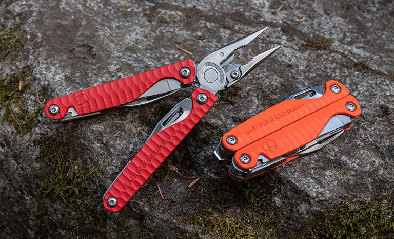An open red Leatherman Charge+ G10 multi-tool laying on a rock next to a closed orange Leatherman Charge+ G10 multi-tool