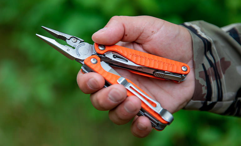 A person with an orange Leatherman Charge+ G10 in hand with the pliers open.
