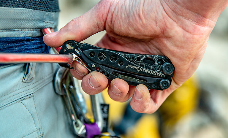 Leatherman Skeletool multi-tool, topo print, connecting carabiner to rock climbing harness