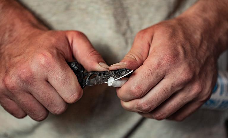 Leatherman freestyle multi-tool, black and silver topo print, knife blade cutting caulk tube