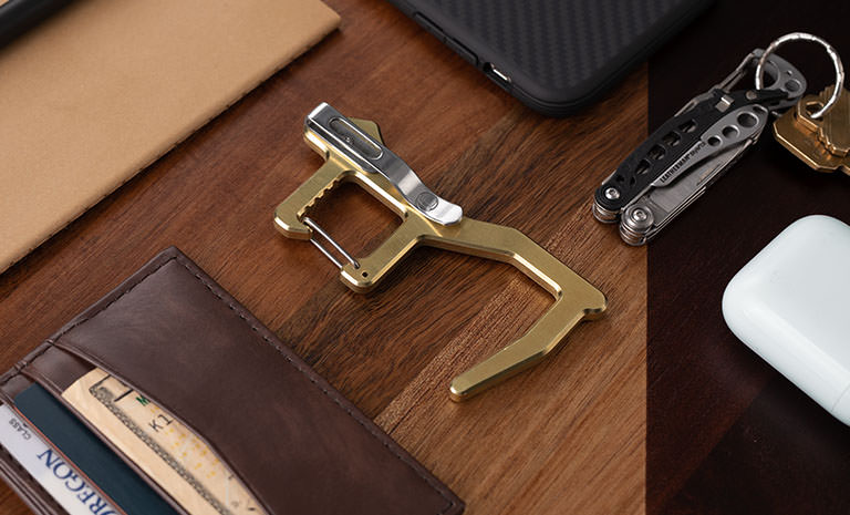 Brass Clean Contact Carabiner on wooden desk with wallet, phone, keys and Leatherman multi-tool