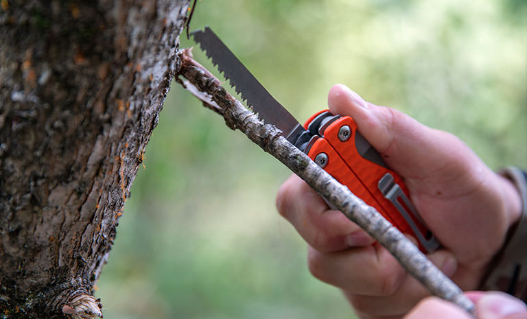 A person using the saw on an orange Leatherman Charge+ G10 to cut a branch