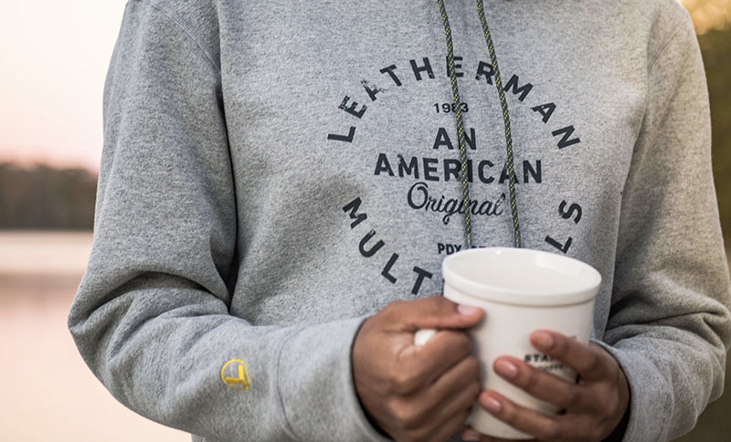 Person holding a mug while wearing a Leatherman Heritage Badge Pullover Hoodie in gray.