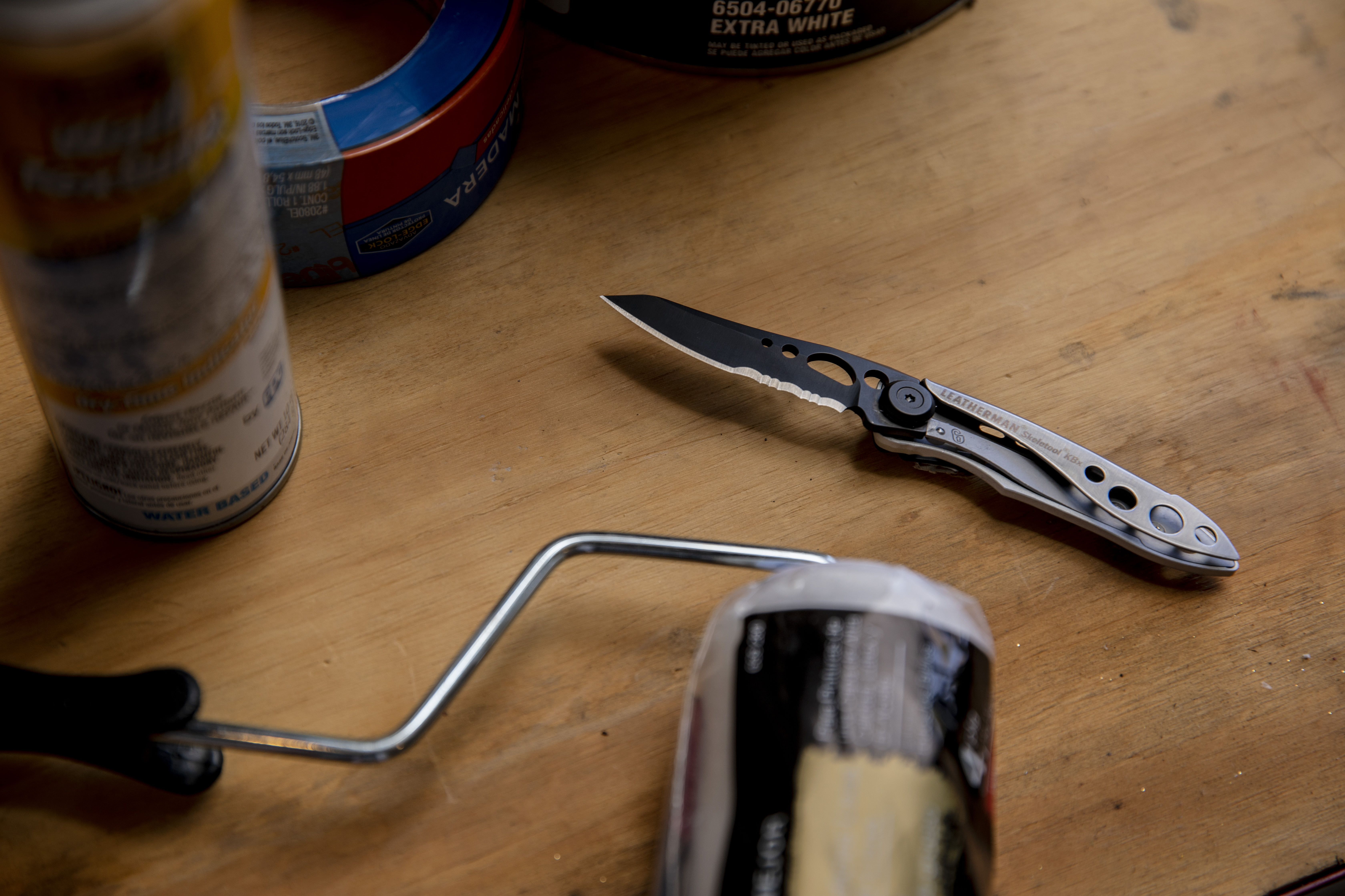 Black and Silver Skeletool KBX with open knife blade on wooden table