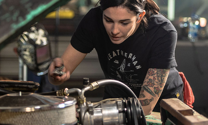 Woman mechanic wears black Leatherman PST Heritage T-Shirt while working under the hood of a vehicle.