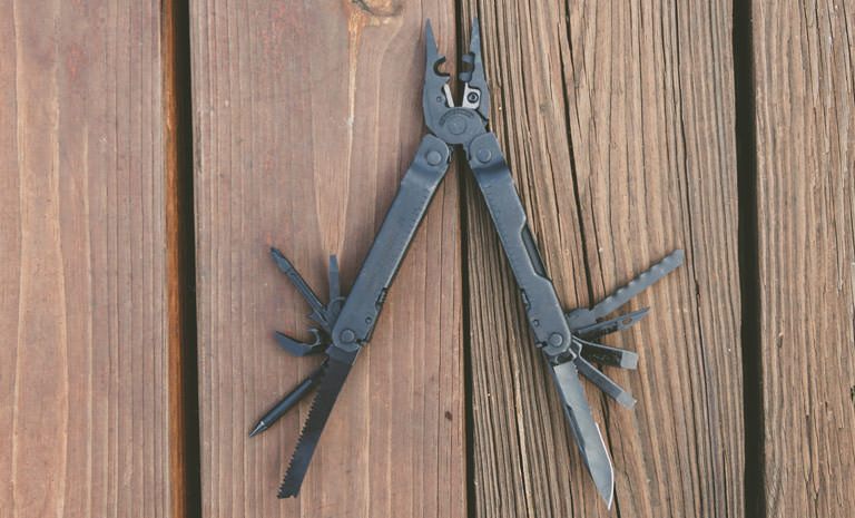 Leatherman super tool 300 eod multi-tool on wooden surface, open view, black, 19 tools