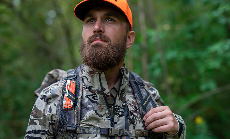 A hunter with an orange Leatherman Charge+ G10 multi-tool strapped to his backpack
