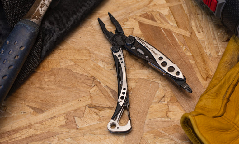 Leatherman black & silver stainless steel skeletool multi-tool fanned on wodden surface