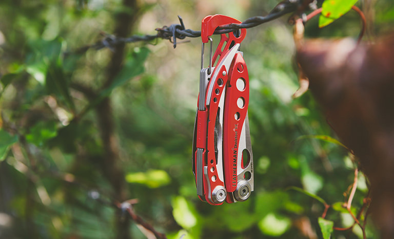Leatherman skeletool rx multi-tool hanging on wire, orange, closed view