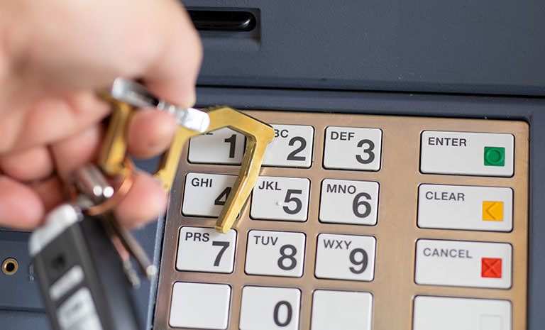 Brass Clean Contact Carabiner being used to press ATM buttons
