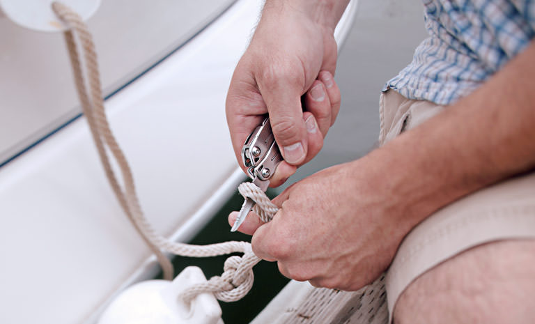 Leatherman sidekick multi-tool in hand, cutting rope on a boat