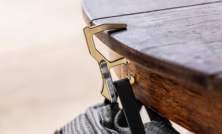 Brass Clean Contact Carabiner hanging a bag off a wooden table