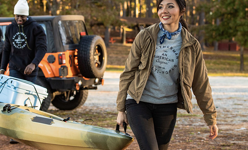 Woman wearing gray Leatherman Heritage Badge Tee helps carry kayak to the water with man wearing black Leatherman Badge Pullover Hoodie.