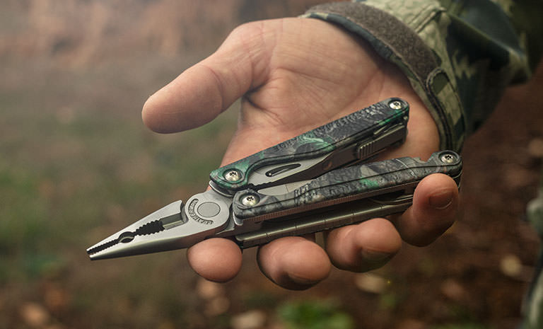 Leatherman Charge TTi multi-tool, Realtree camo print, pliers in hunters hand