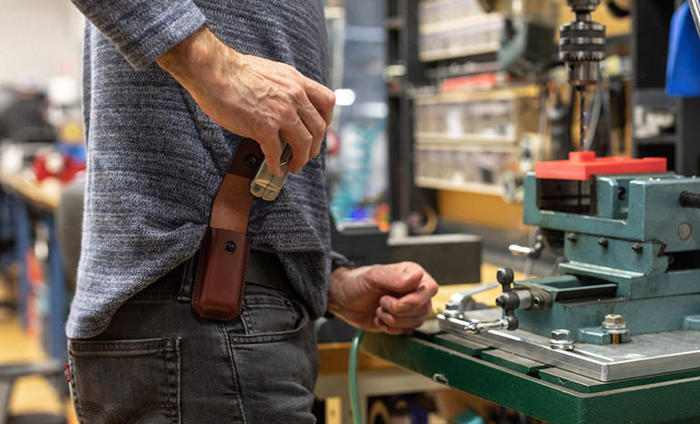 Man at Workbench Pulling Leatherman Rebar Multitool Out of Ainsworth Leather Sheath