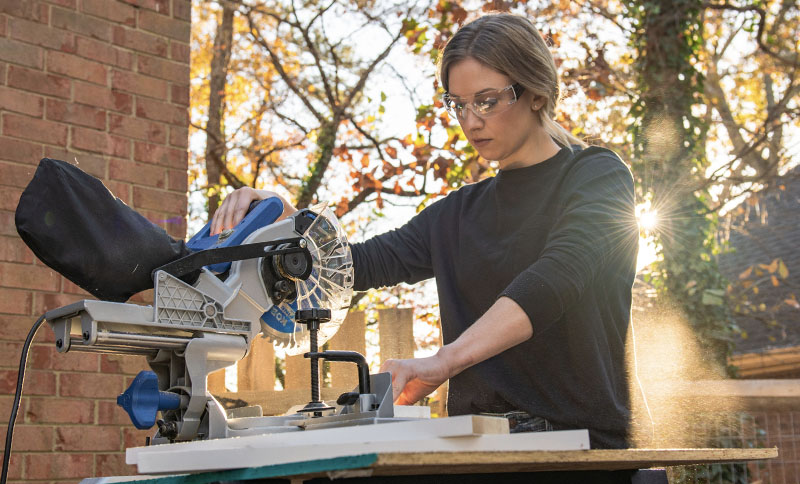 Woman wearing a Leatherman Basics Long Sleeve shirt in black operates a miter saw in backyard.