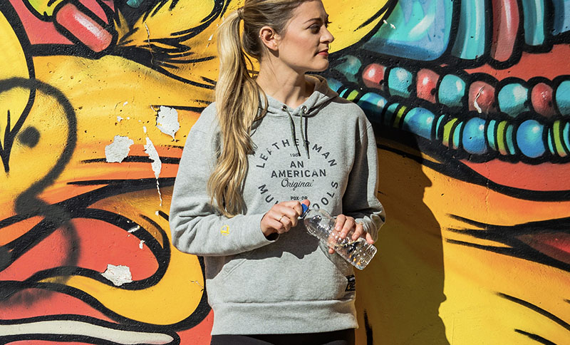 Woman holding water bottle stands against mural wall wearing a gray Leatherman Heritage Badge Pullover Hoodie.