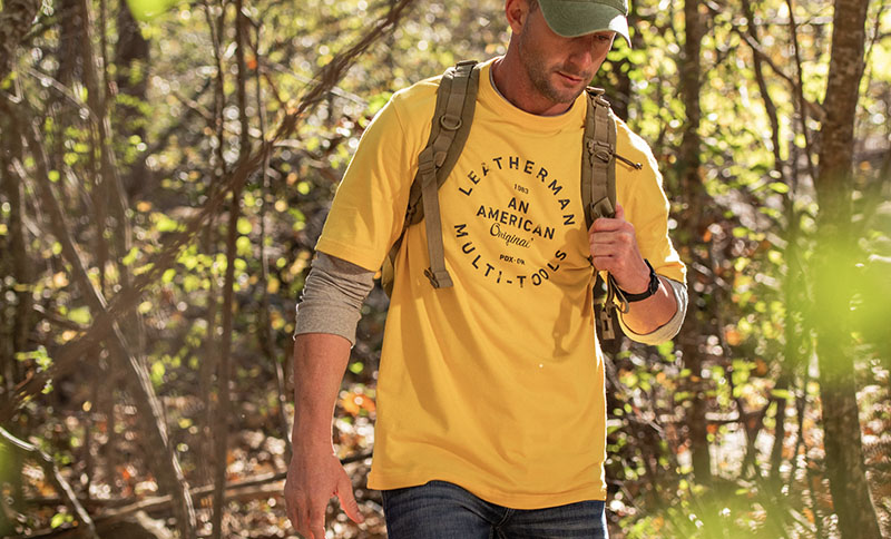 Man hiking through forest wearing Leatherman Heritage Badge Tee in yellow.